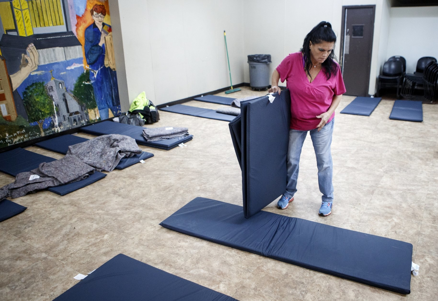 Kim Stewart helps set up mats at the Chattanooga Community Kitchen on Tuesday, Jan. 29, 2019 in Chattanooga, Tenn. The winter shelter at the Chattanooga Community Kitchen opens every night from December through March and houses more than a hundred people on the coldest nights. (C.B. Schmelter/Chattanooga Times Free Press via AP)