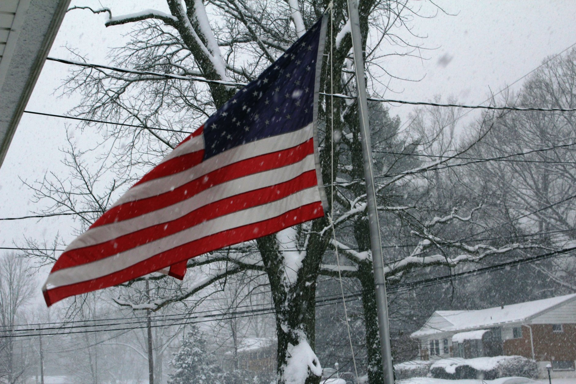 The American flag waves as snow falls in Rockville, Maryland. (Courtesy Steve Barbara)