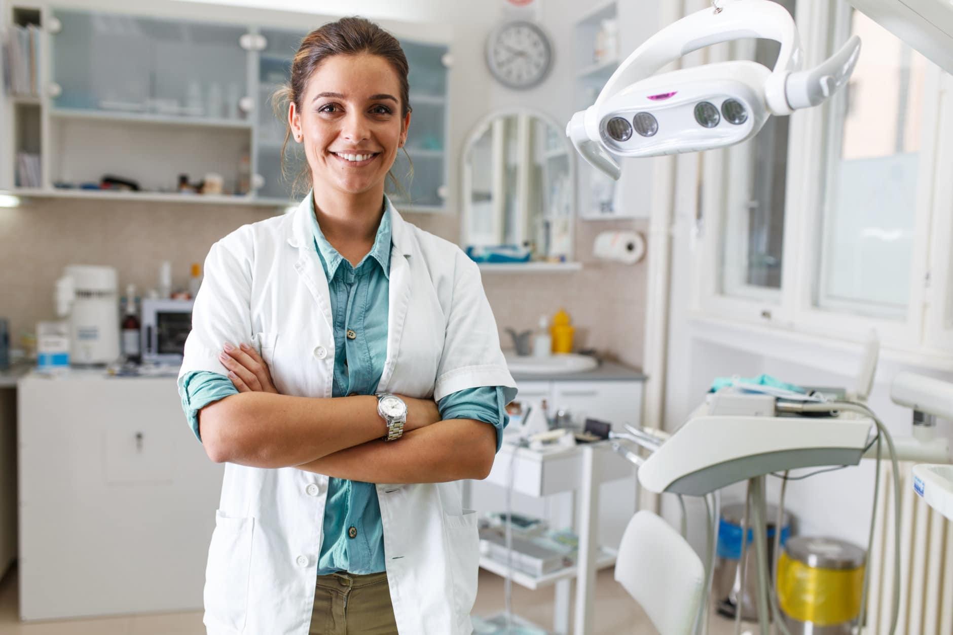 Portrait of female dentist .She standing in her dentist office..