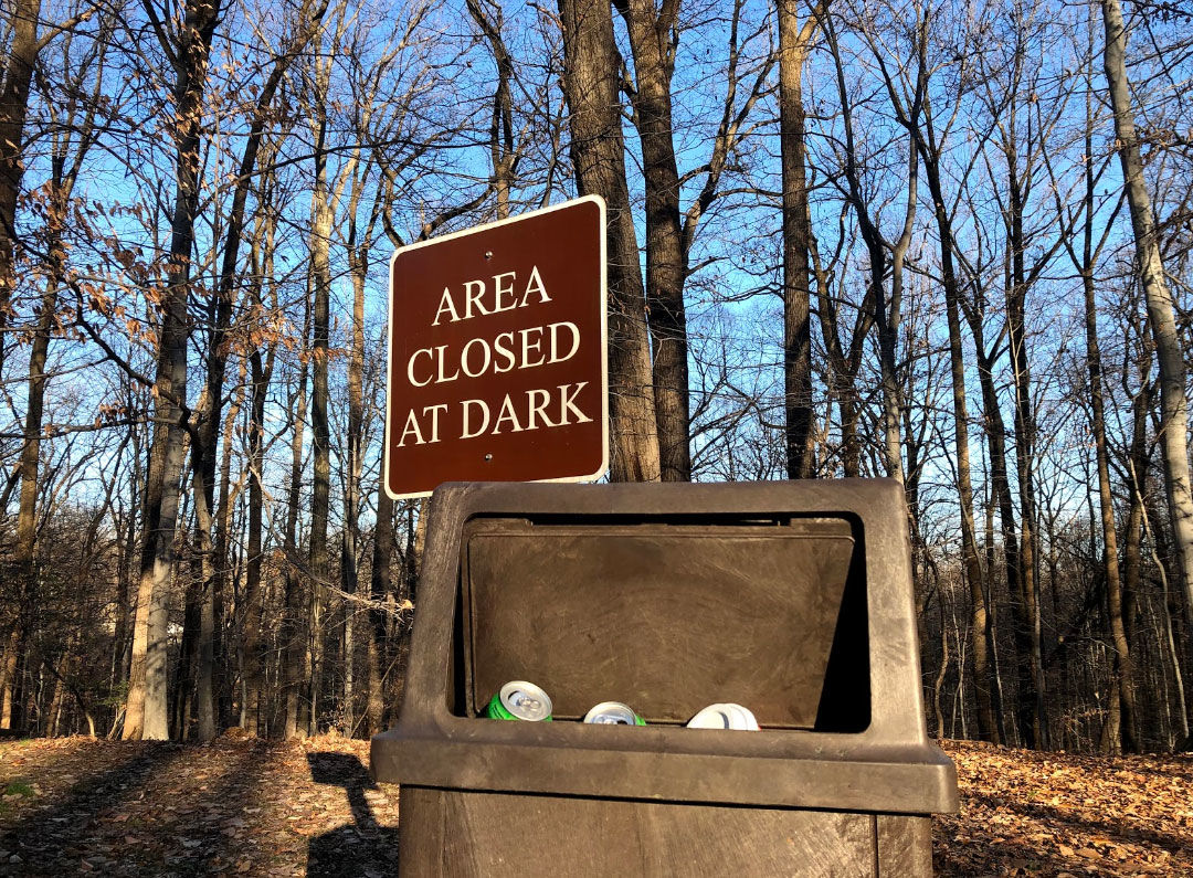 The lid of a trash can is left open as trash peeks out at Rock Creek Park on Thursday, Jan. 10, 2019. (WTOP/Mike Murillo)