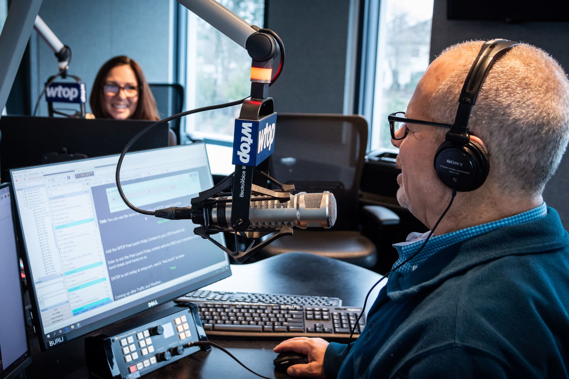 Morning anchors Joan Jones and Bruce Alan go through a dry run of a standard news broadcast using the Glass Enclosed Nerve Center's new equipment. WTOP's news and advertising management softwares also saw upgrades, and audio engineers trained anchors how to use the new technology in the days leading up to the move. (WTOP/Alejandro Alvarez)