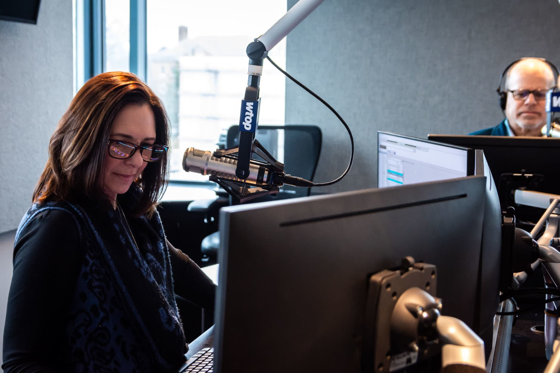 Anchor Joan Jones tests WTOP's new ad management and audio playback software during an off-air practice run on Jan. 29. While the majority of WTOP's broadcast is recorded live in-house, pre-recorded reporter stories, segment transitions and ads are played back by anchors using the main studio's mixing board. (WTOP/Alejandro Alvarez)