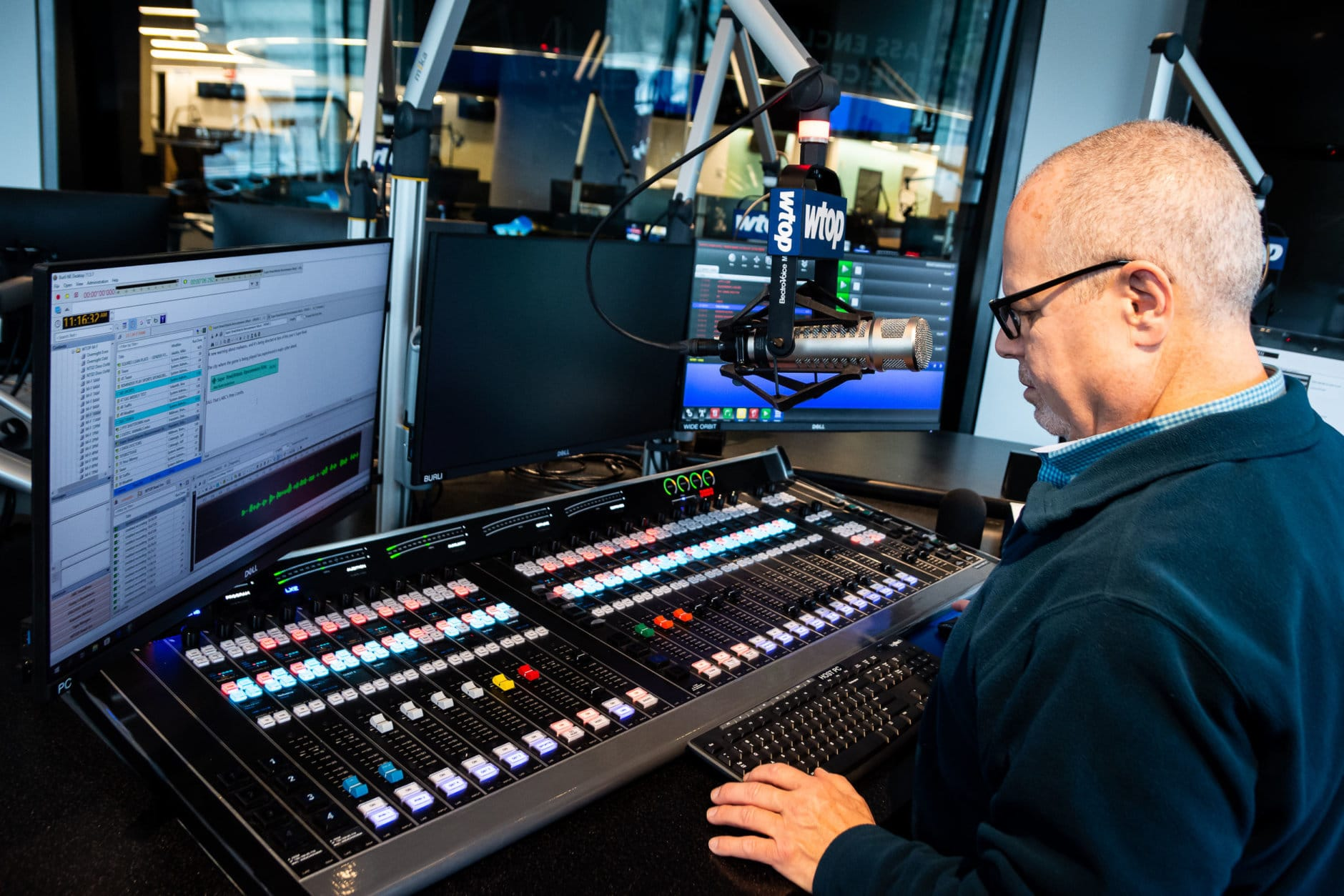 WTOP anchor Bruce Alan mans the Glass-Enclosed Nerve Center's new mixing board, which controls audio levels and can feed listener calls into the broadcast. (WTOP/Alejandro Alvarez)