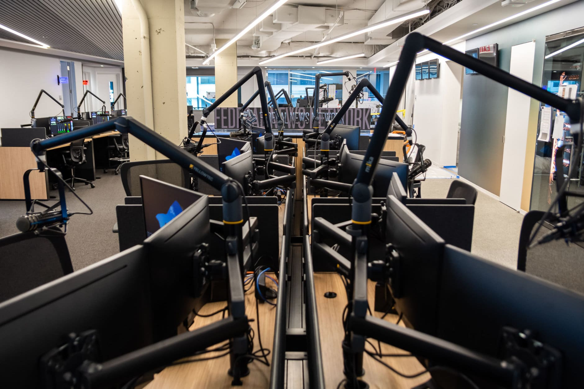 The new office space at 5425 Wisconsin Avenue will be the first time that WTOP and its sister station for federal employees, Federal News Network (FNN), will be produced from the same floor. FNN's new nameplate is visible here, behind a forest of retractable microphone arms. (WTOP/Alejandro Alvarez)