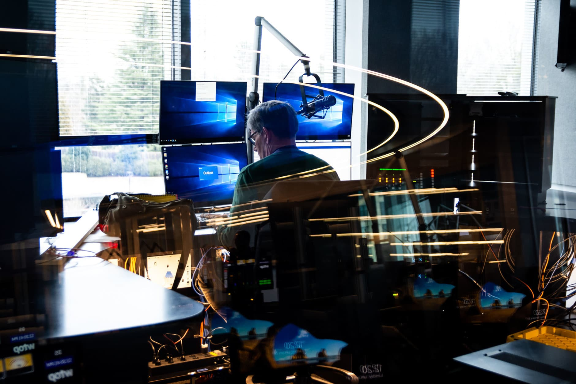 WTOP traffic reporter Ian Crawford logs on to his station in WTOP's new Traffic Center for a test-run. The new Traffic Center is twice as large as the first, and features twice as many screens. It'll also feature another first for the traffic team: A glass window overlooking the rest of the newsroom. (WTOP/Alejandro Alvarez)