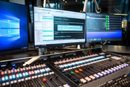 A behind-the-scenes view of the new Glass-Enclosed Nerve Center as an anchor would see it during a broadcast. Pictured at center is Burli, the news management software WTOP's radio editors use to ferry scripts and news reports to anchors inside the main studio. (WTOP/Alejandro Alvarez)