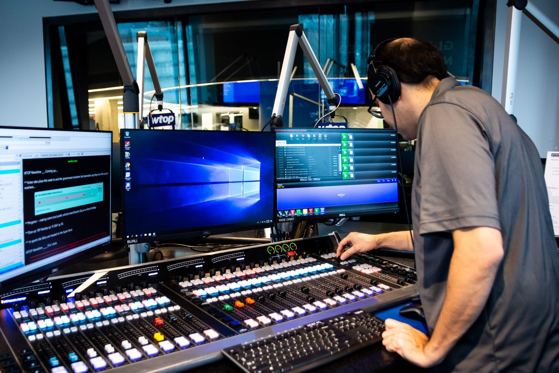 WTOP's Mike Murillo programs the Glass-Enclosed Nerve Center's control console before anchors arrive for a practice run on Jan. 29. The starship-like circular bridge which seats the station's editors can be seen through the glass in the background. Though the studio is sound-proofed, editors can talk with the editors through an intercom system. (WTOP/Alejandro Alvarez)