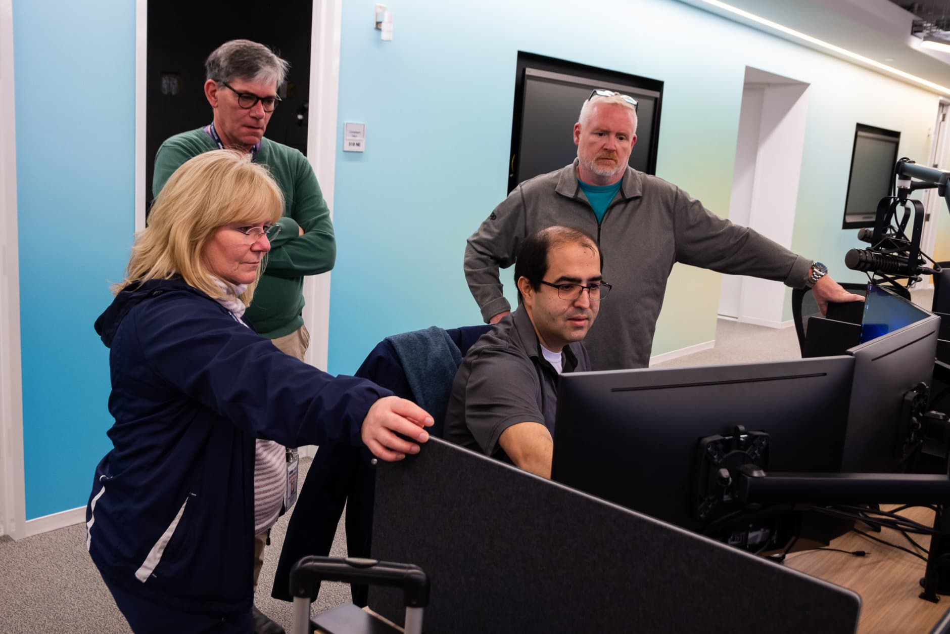 WTOP reporter Mike Murillo (center) leads WTOP's morning traffic team (from left, Mary de Pompa, Ian Crawford and Jack Taylor) through a demonstration of the newsroom's new virtual system for taking listener phonecalls. (WTOP/Alejandro Alvarez)