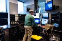 "Traffic reporter Ian Crawford runs through an off-air test of the Traffic Center's reports ""on the 8's."" The vertical window at center-right offers a the Traffic Center a view into the new Glass-Enclosed Nervce Center. The traffic center can communicate with the radio editor and anchors in the main studio through an intercom system.(WTOP/Alejandro Alvarez)"