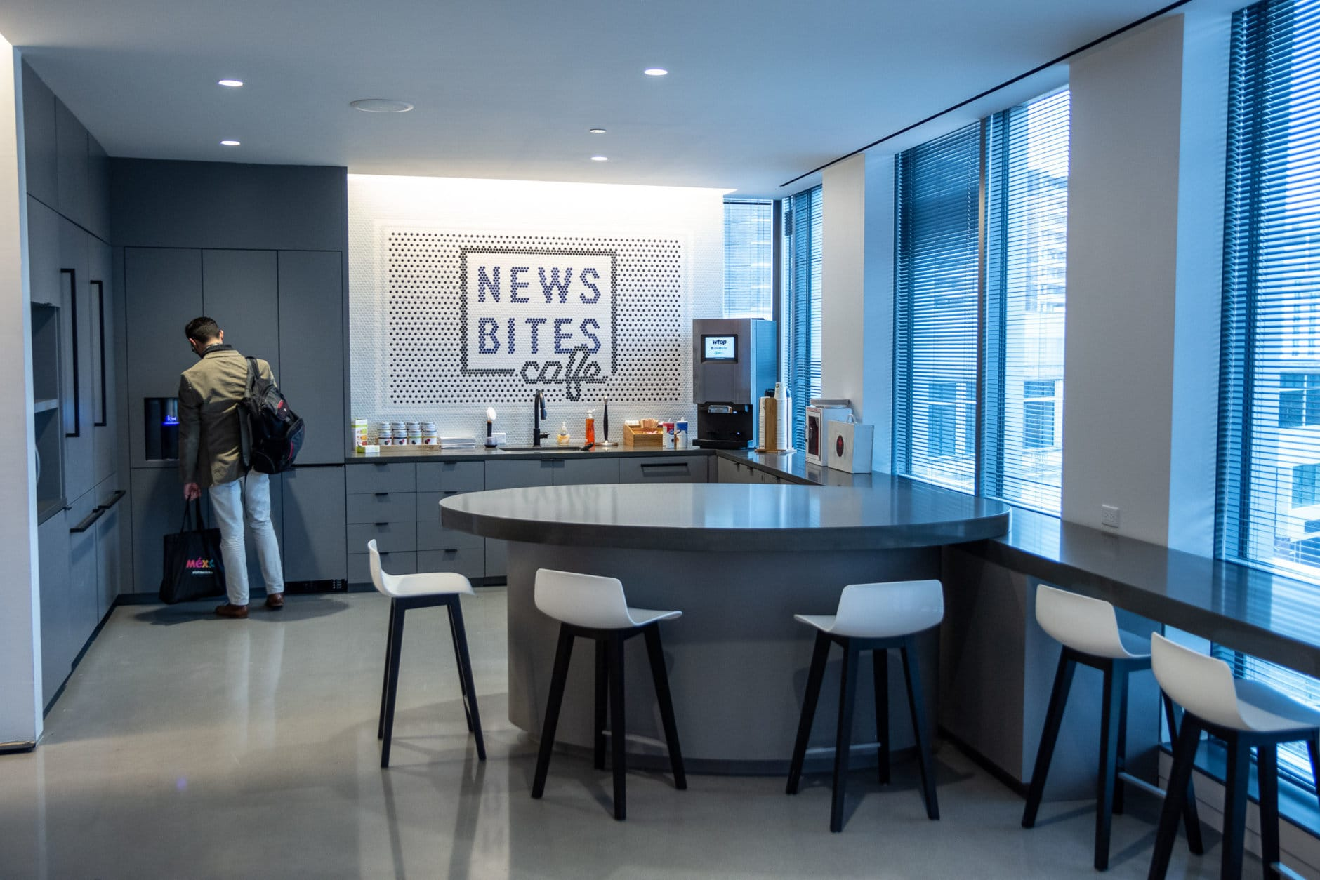 "The new office cafe, News Bites, features free coffee, tea and carbonated water dispensers, as well as plenty of seating space with a view of Friendship Heights. Its name was chosen by vote, beating runner-up ""#Food4Thought."" (WTOP/Alejandro Alvarez)"