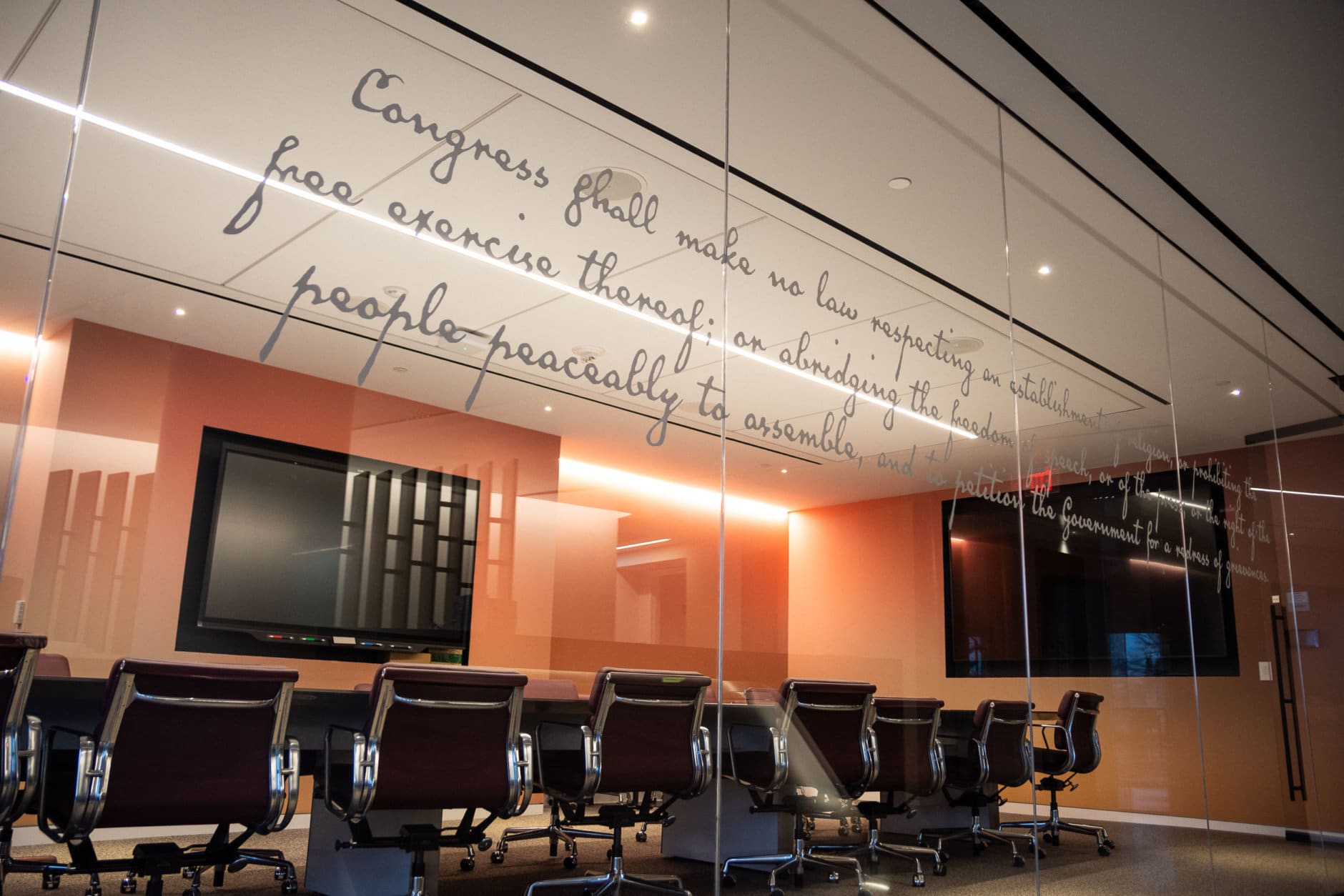 Like the Idaho Avenue building, the First Amendment will feature prominently in the new office. Pictured, the 45 words which ensrine five freedoms are stenciled on glass panels facing the reception area. (WTOP/Alejandro Alvarez)