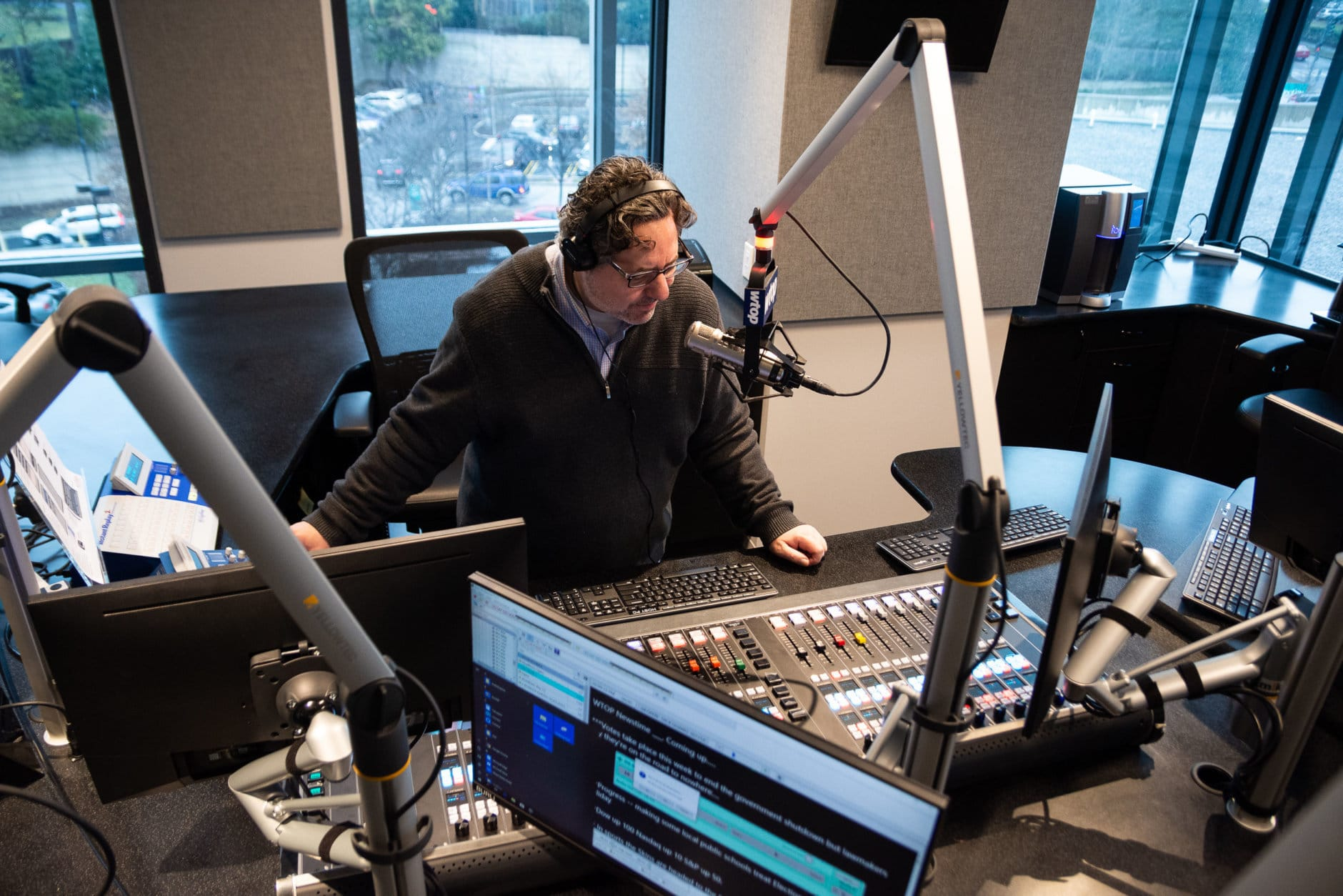 WTOP anchor Dimitri Sotis familiarizes himself with the new Glass-Enclosed Nerve Center. (WTOP/Alejandro Alvarez)