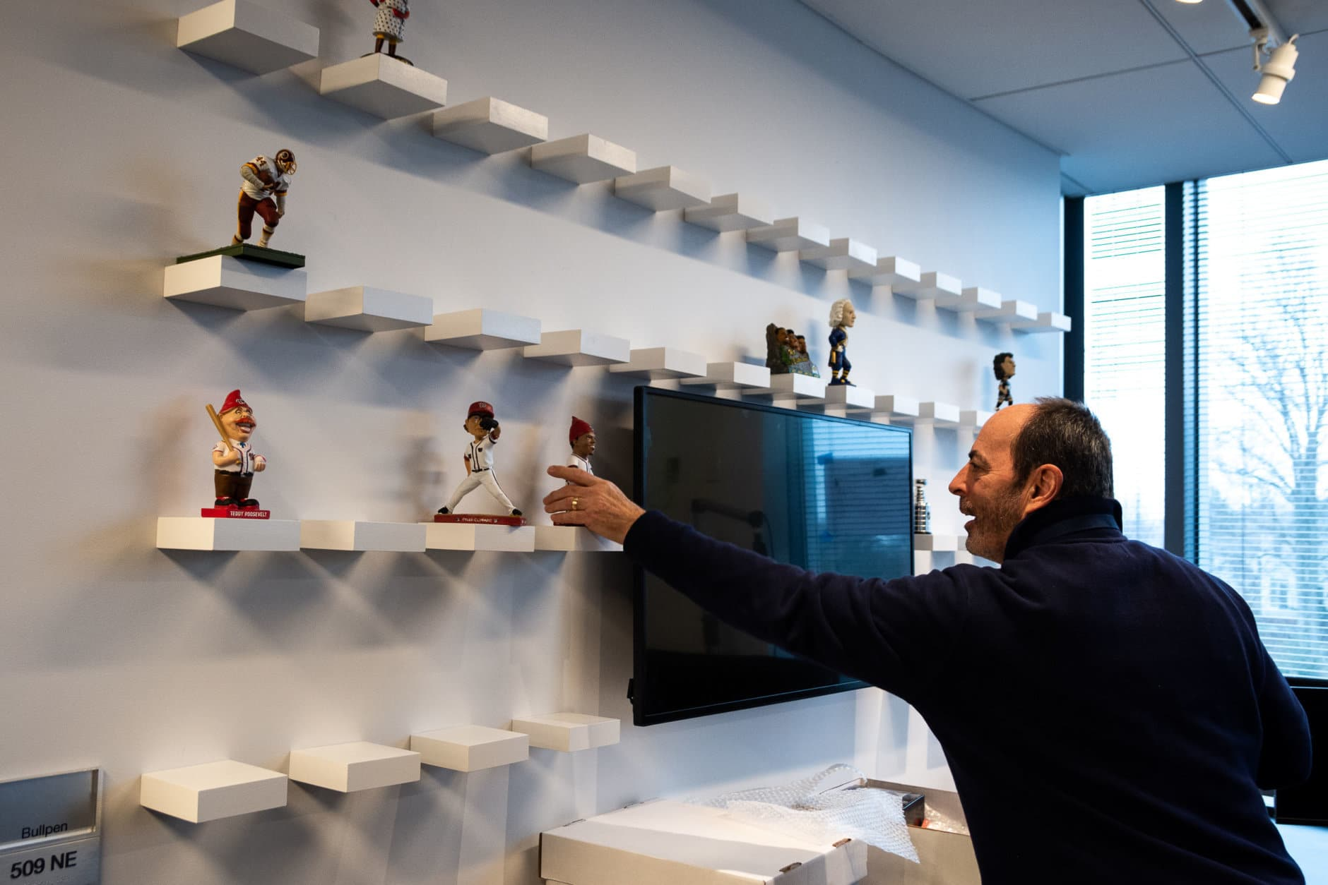 The start of a new era: WTOP sports anchor Jonathan Warner brings the sport desk's army of bobbleheads to their home. (WTOP/Alejandro Alvarez)