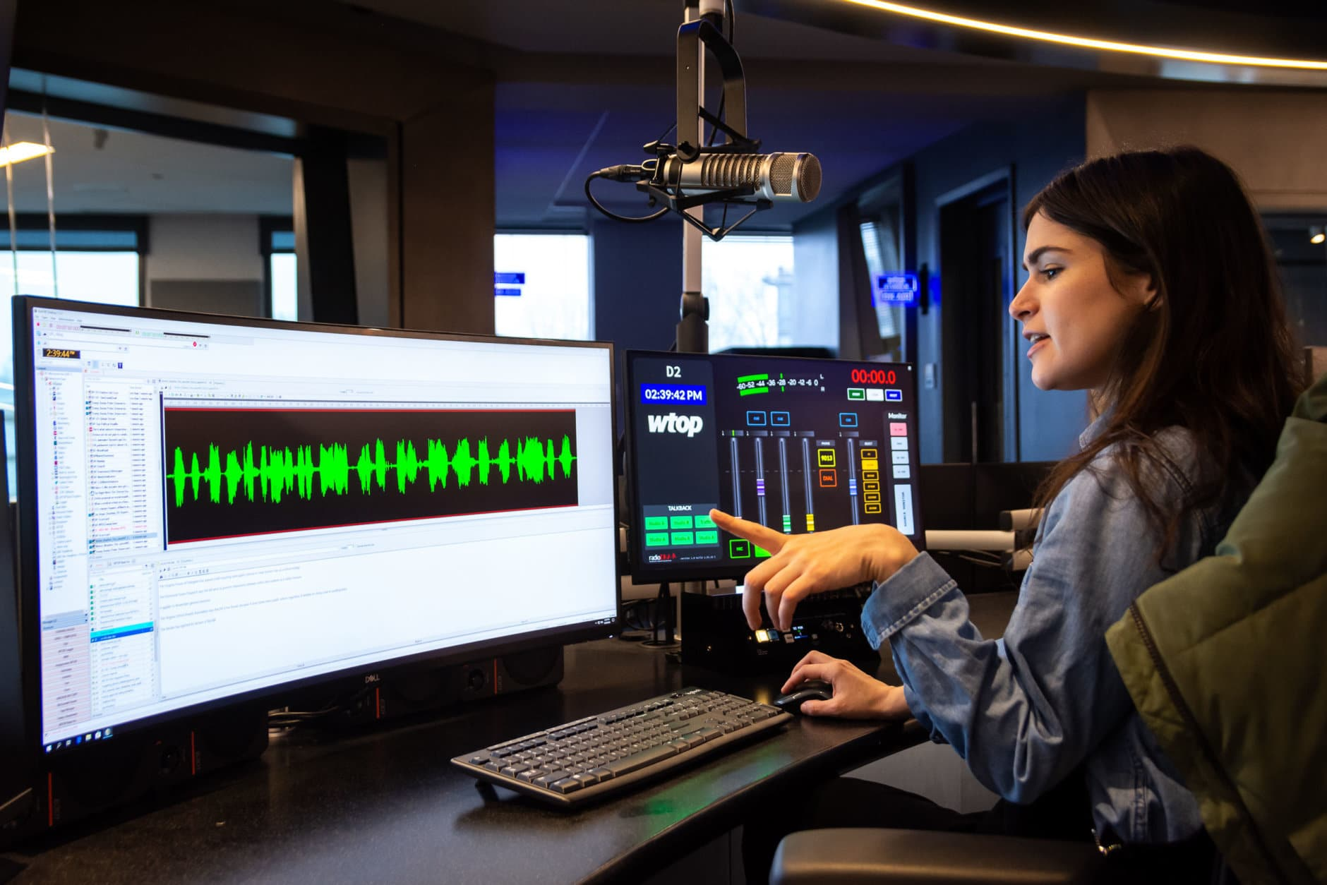 WTOP night editor Anna Isaacs at her work station on Jan. 29. The Radio Editor handles the minute-to-minute flow and coverage of news, including the order of stories in the hourly lineup. They also seek out and book interviews, and direct anchors through breaking news coverage. Like the original WTOP newsroom, the new Radio Editor station has a direct line of sight into the Glass-Enclosed Nerve Center, and can communicate with the anchors through intercom. (WTOP/Alejandro Alvarez)