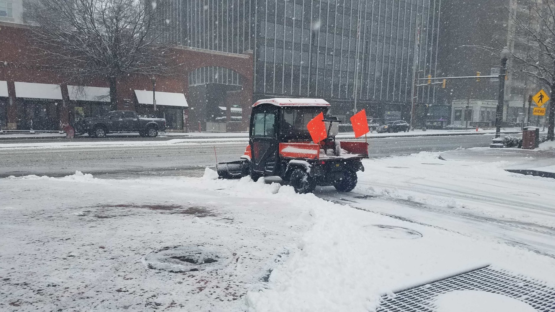 A plow fights the buildup of snow in Chevy Chase. (WTOP/Will Vitka)