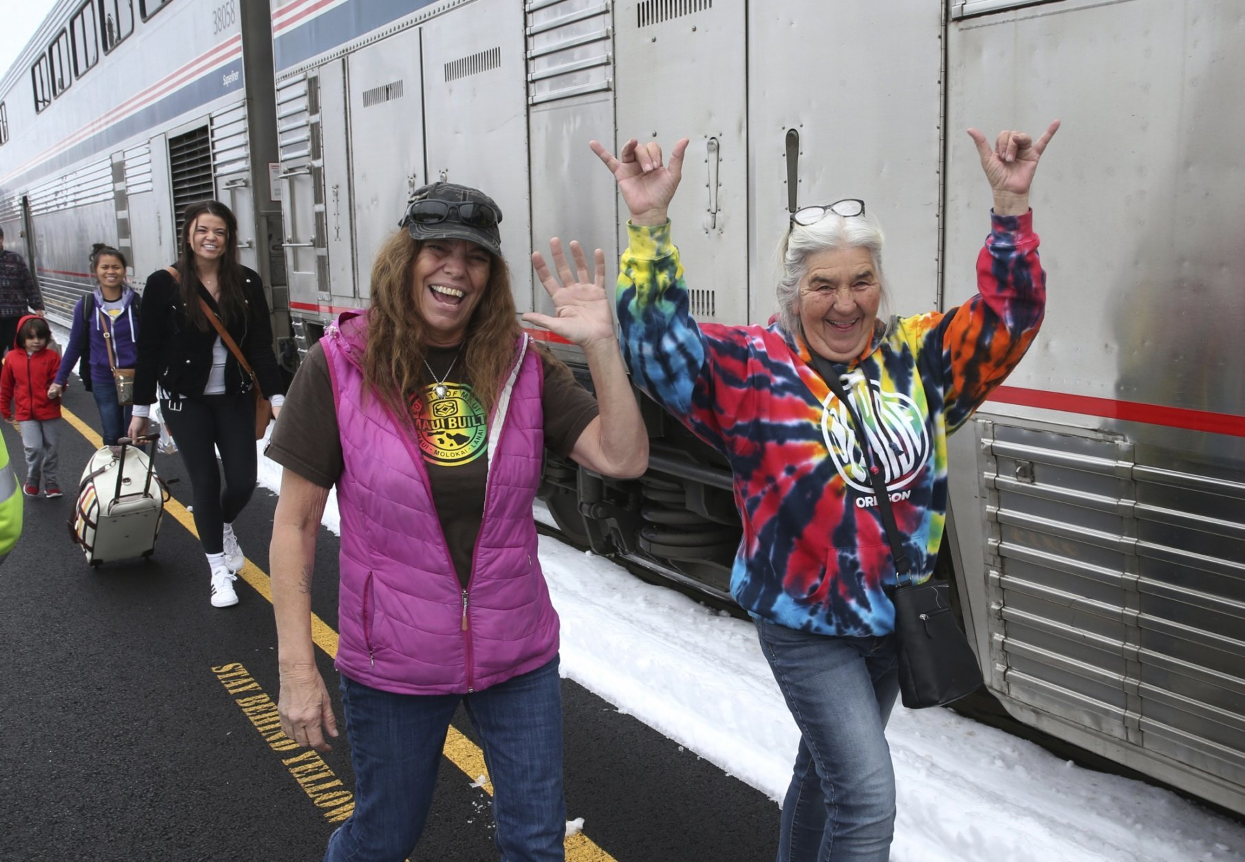 Patricia Bailey, center, and Annette Saba, right, celebrate as they disembark an Amtrak passenger train in Eugene, Ore. Tuesday, Feb. 26, 2019.  The train traveling from Seattle to Los Angeles with 183 passengers got stranded in the snowy mountains of Oregon for at least 36 hours, putting a strain on passengers as food, patience and even diapers ran short.  (AP Photo/Chris Pietsch)