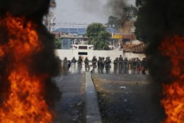 Bolivarian National Guard troops man a barricade blocking access to the Francisco De Paula Santander international bridge in Urena, Venezuela, on the border with Colombia, Saturday, Feb. 23, 2019. Venezuela's National Guard fired tear gas on residents clearing a barricaded border bridge between Venezuela and Colombia on Saturday, heightening tensions over blocked humanitarian aid that opposition leader Juan Guaido has vowed to bring into the country over objections from President Nicolas Maduro. (AP Photo/Fernando Llano)