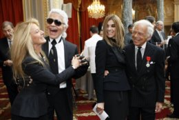 US fashion designer Ralph Lauren, right, awarded the Chevalier of the Legion of Honor, one of France's most prestigious distinctions, and Editor-in-Chief of the French edition of Vogue, Carine Roitfeld, second right , watch as German fashion designer Karl Lagerfeld dances with his wife Ricky Lauren during a ceremony at the Elysee Palace in Paris, Thursday, April 15, 2010. (AP Photo/Francois Mori, Pool)