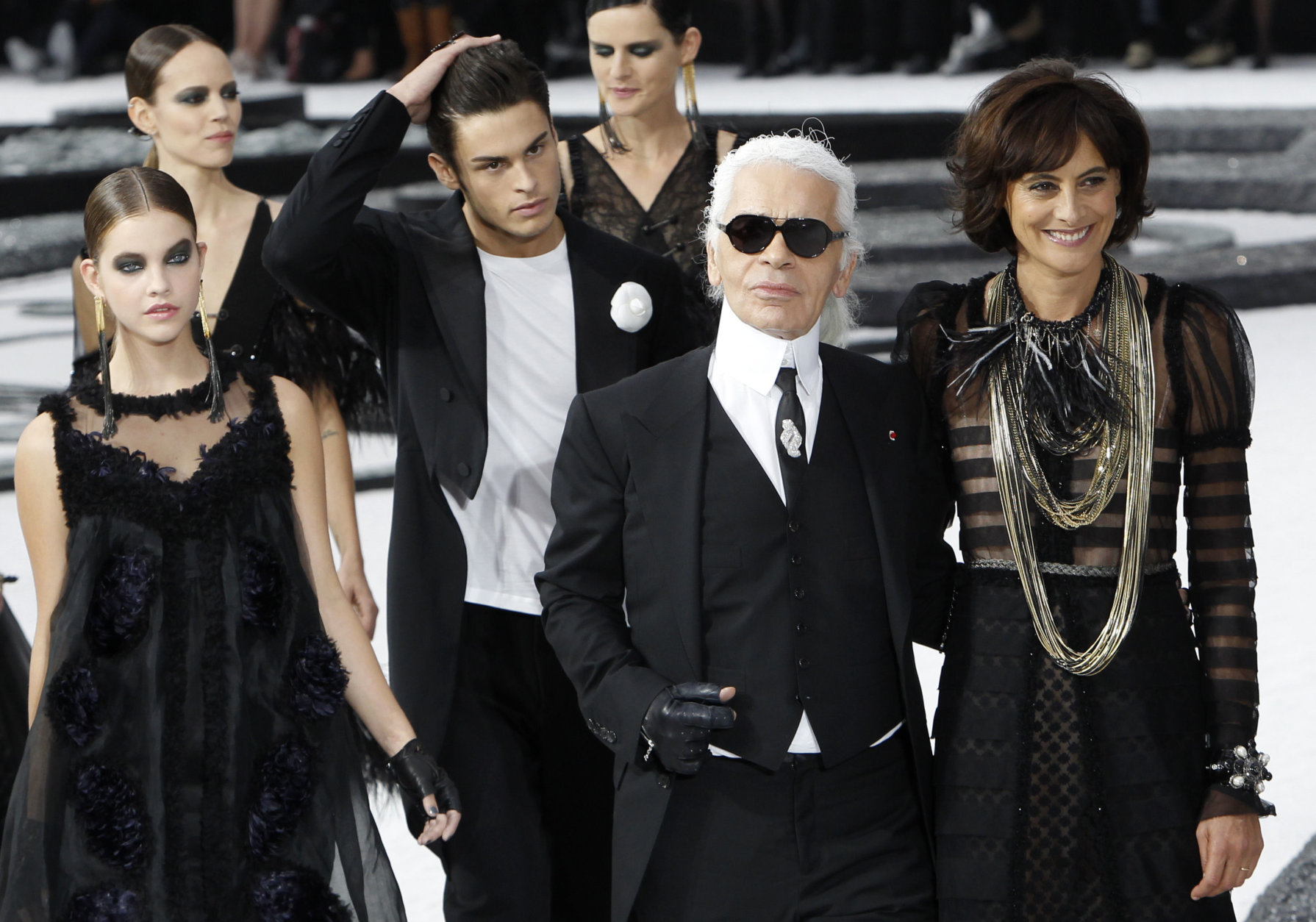 German fashion designer Karl Lagerfeld, 2nd from right, and French former model and now designer Ines de la Fressange, right, flanked with models, take the catwalk, at the Grand Palais museum, at the end of Lagerfeld's spring-summer 2011 ready to wear collection for Chanel, presented in Paris, Tuesday, Oct. 5, 2010. (AP Photo/Christophe Ena)