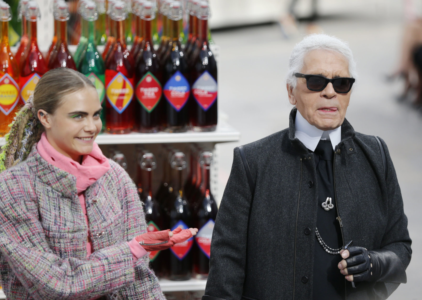 Model Cara Delevingne gestures towards German fashion designer Karl Lagerfeld after the presentation of Chanel's ready to wear fall/winter 2014-2015 fashion collection presented in Paris, Tuesday, March 4, 2014. (AP Photo/Jacques Brinon)