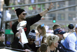 New England Patriots' Tom Brady rides beside the trophy as the team parades through downtown Boston, Tuesday, Feb. 5, 2019, to celebrate their win over the Los Angeles Rams in Sunday's NFL Super Bowl 53 football game in Atlanta. (AP Photo/Michael Dwyer)
