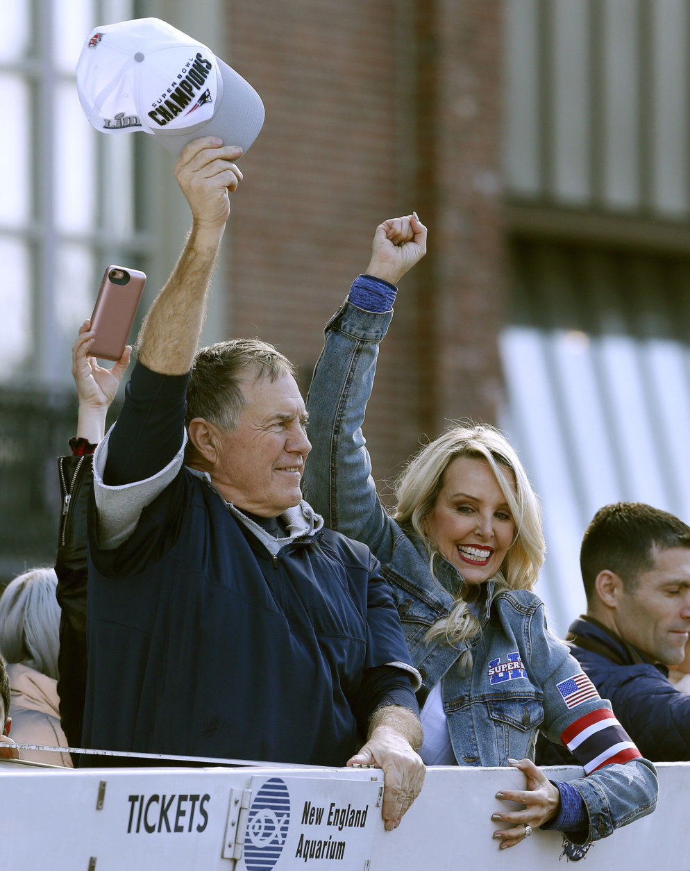 New England Patriots head coach Bill Belichick and partner Linda Holliday wave as the team parades through downtown Boston, Tuesday, Feb. 5, 2019, to celebrate their win over the Los Angeles Rams in Sunday's NFL Super Bowl 53 football game in Atlanta. (AP Photo/Michael Dwyer)