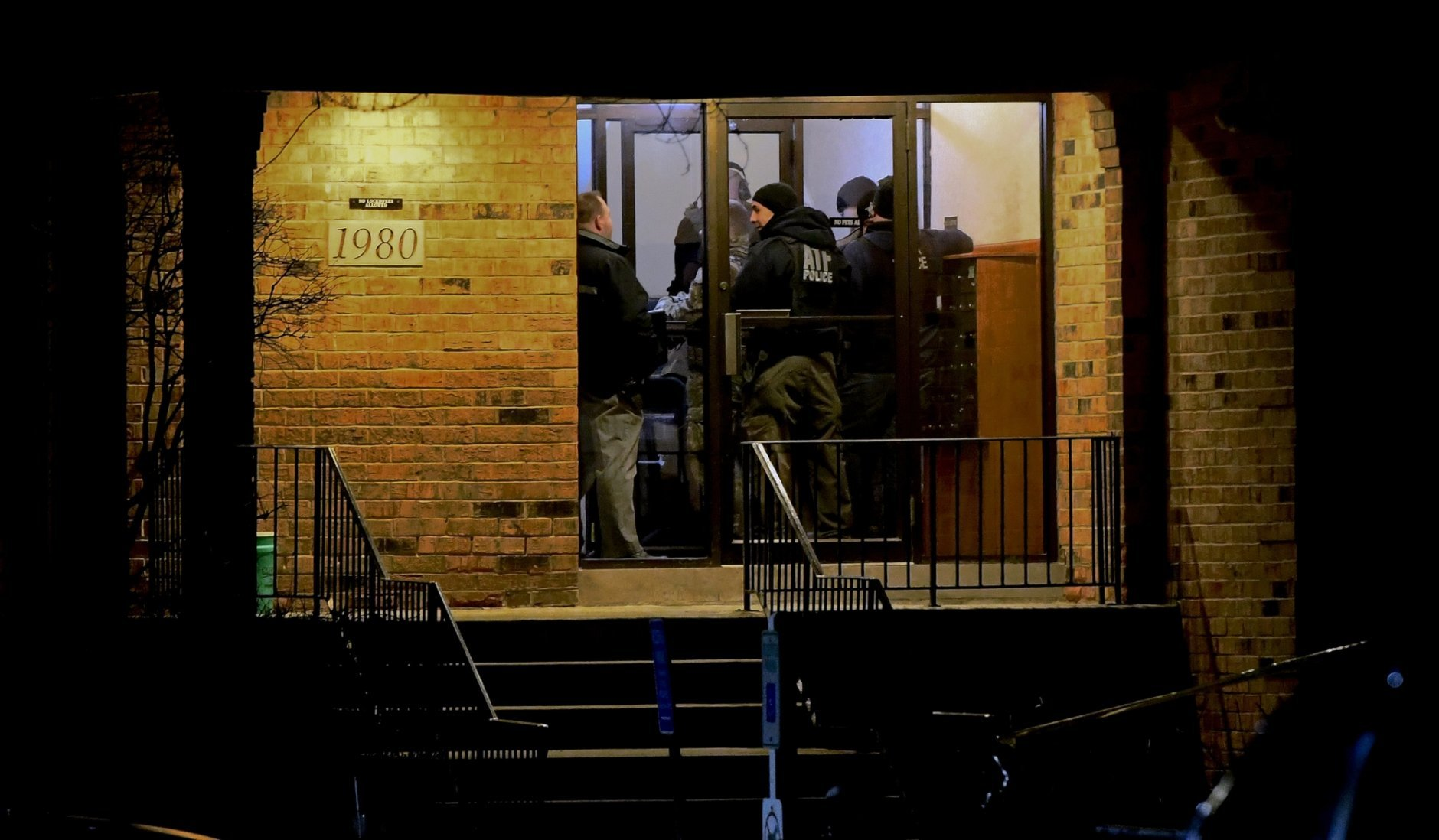 Investigators enter an apartment building Friday, Feb. 15, 2019, in Aurora, Ill., where a man who police say fatally shot several people and injured police officers at a manufacturing plant in Aurora is believed to have lived. (AP Photo/Matt Marton)