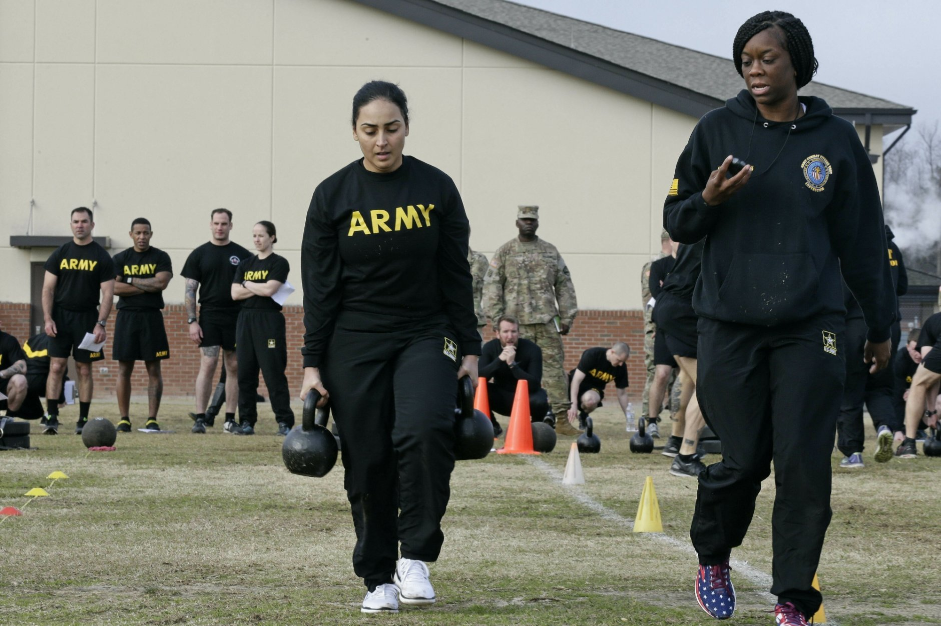 In this  Jan. 8, 2019, photo, U.S Army Staff Sgt. Idis Arroyo,left, carries weights while training to serve as an instructor in the new Army combat fitness test at Fort Bragg, N.C. The new test is designed to be a more accurate test of combat readiness than the current requirements. (AP Photo/Gerry Broome)