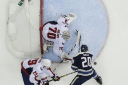 Washington Capitals' Braden Holtby, top, makes a save against Columbus Blue Jackets' Riley Nash, right, as Christian Djoos, of Sweden, trails the play during the first period of an NHL hockey game Tuesday, Feb. 12, 2019, in Columbus, Ohio. (AP Photo/Jay LaPrete)