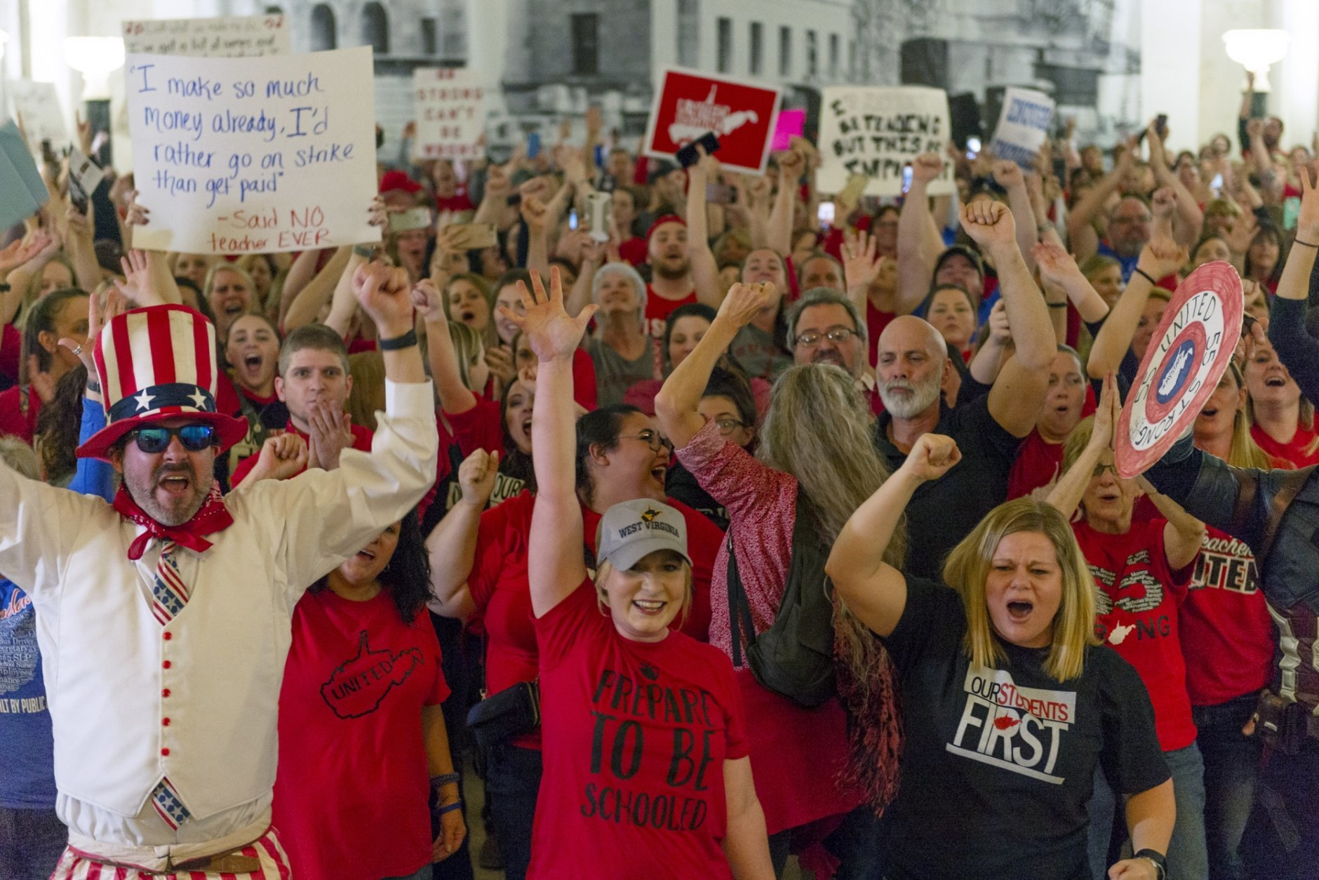 Teachers and school personnel celebrate after the House of Delegates passed a motion to postpone a vote on Senate Bill 451 indefinitely at the West Virginia State Capitol in Charleston, W.Va., during a statewide teachers' strike on Tuesday, Feb. 19, 2019. (Craig Hudson/Charleston Gazette-Mail via AP)