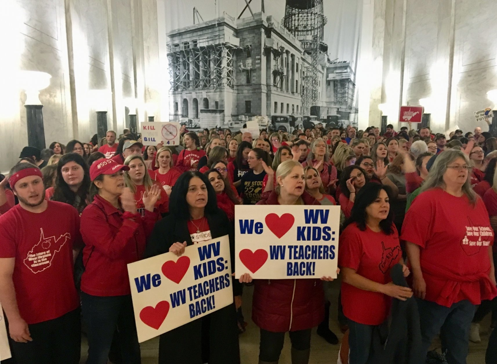 Striking West Virginia teachers and supporters rally outside the House of Delegates chambers Tuesday, Feb. 19, 2019, at the state Capitol in Charleston, W.Va. Teachers are opposed to a complex education bill making its way through the Legislature. (AP Photo/John Raby)