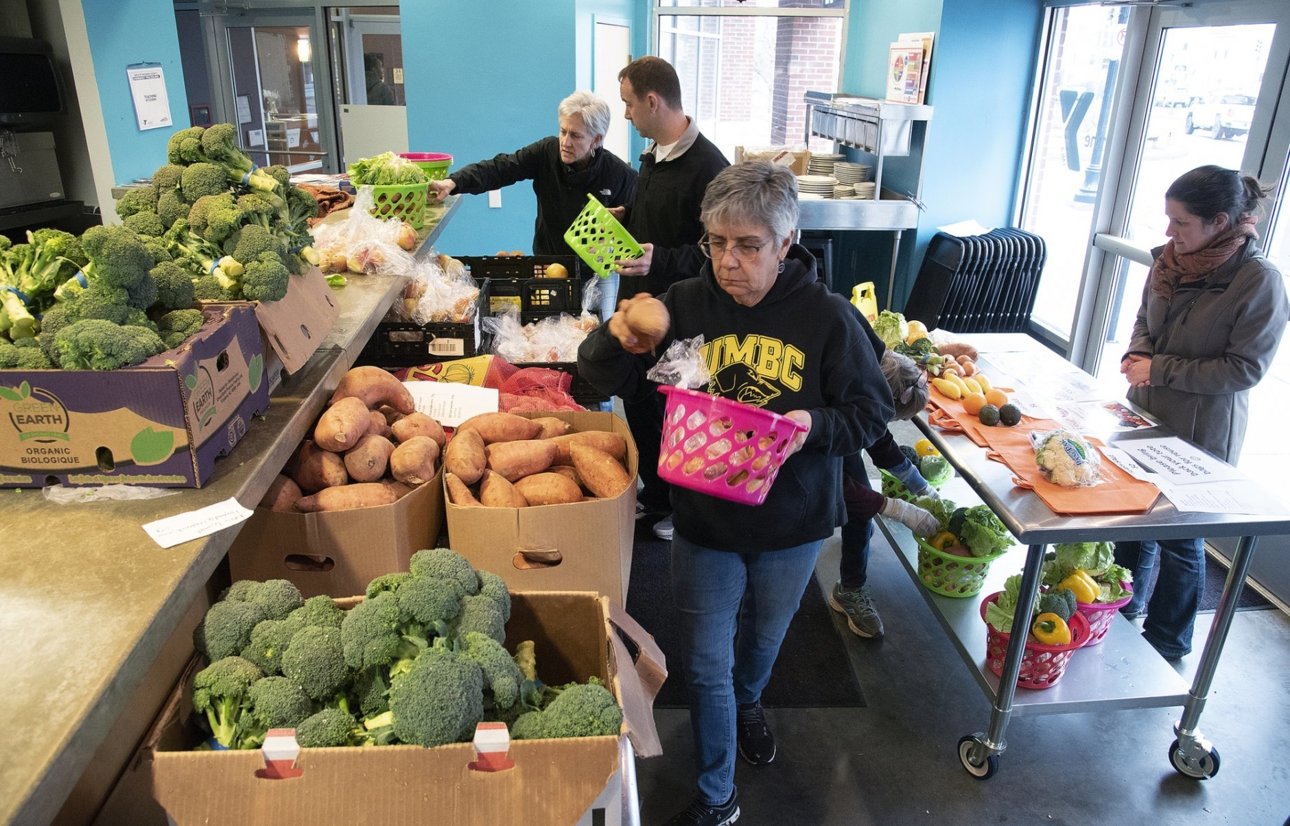 In this Wednesday, Feb. 6, 2019 photo, volunteer Peggy Haser, center, fills a basket with fresh vegetables at the Hungry Harvest reduced-cost produce market at the YMCA of Frederick County's teaching kitchen in Frederick, Md. (Dan Gross/The Frederick News-Post via AP)