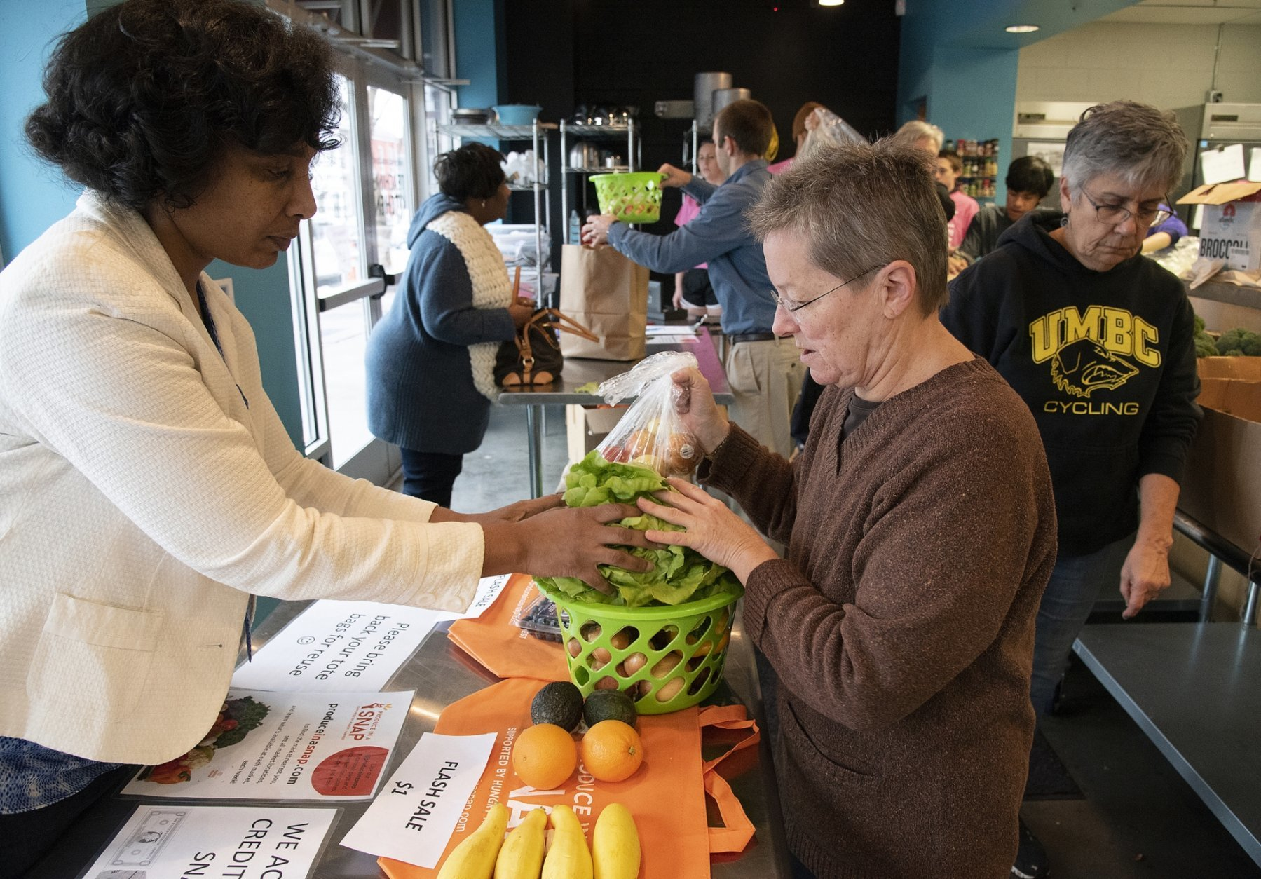 In this Wednesday, Feb. 6, 2019 photo, Shannon Coles, left, picks out vegetables and volunteer Ginny Skelley packs her basket at the Hungry Harvest reduced-cost produce market at the YMCA of Frederick County's teaching kitchen in Frederick, Md. (Dan Gross/The Frederick News-Post via AP)