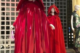 """This Jan. 31, 2019 cell phone photo shows a red patent leather-hooded cape by Rei Kawakubo, foreground and a late 18th century scarlet cloak with an attached hood, which are part of the """"Exhibitionism: 50 Years of The Museum at FIT,"""" opening Friday, Feb. 8 in New York. (AP Photo/Jocelyn Noveck)"""