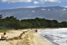 """In this Monday, Feb. 11, 2019 photo, with snow-capped Haleakala serving as a backdrop, Paia Maui's Scott Picton, left, plays a guitar and Saskatchewan's Shannon and Dan Runcie walk on Sugar Beach in South Maui, Hawaii. The summit area of Haleakala National Park is closed because of """"extreme winter conditions."""" Park officials said Tuesday, Feb. 12, 2019, that snow, ice, fallen trees and rocks are making the area dangerous. (Matthew Thayer/The News via AP)"""