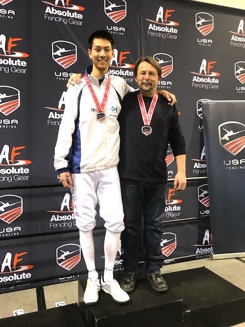 Justin Haddad celebrates his gold medal match in Cadet Men's Epee with DC Fencers Club Head Coach Janusz Smolenski (Courtesy D.C. Fencer's Club)
