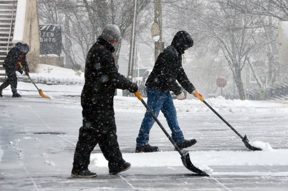 Maintenance crews shovel snow in Tenleytown. (WTOP/Dave Dildine)