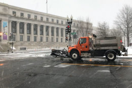 A snow plow makes its way through the District near Union Station. (WTOP/Steve Dresner)
