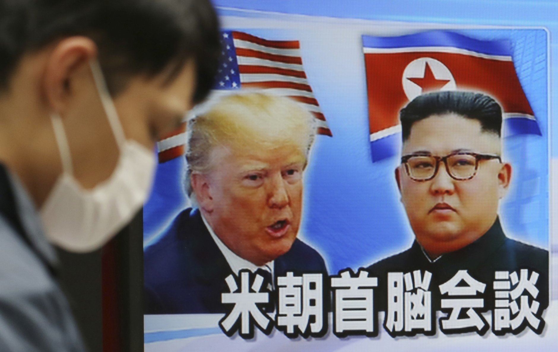 A man walks past a TV screen showing North Korean leader Kim Jong Un, right, and U.S. President Donald Trump in a news program in Tokyo, Wednesday, Feb. 27, 2019. Kim is expected to meet with Trump for a second summit over the next two days in Hanoi, Vietnam. (AP Photo/Koji Sasahara)