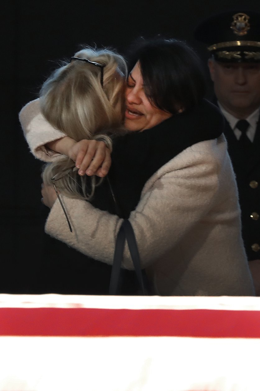 Rep. Debbie Dingell, D-Mich., left, hugs Rep. Rashida Tlaib, D-Mich., at the casket of her husband and former Rep. John Dingell, lying in repose in Dearborn, Mich., Monday, Feb. 11, 2019. John Dingell, the longest-serving member of Congress in American history, was first elected in 1955 and retired in 2014. The Democrat was 92. (AP Photo/Paul Sancya)