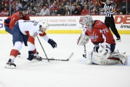Washington Capitals goaltender Braden Holtby (70) stops the puck against Florida Panthers left wing Jonathan Huberdeau (11) during the second period of an NHL hockey game, Saturday, Feb. 9, 2019, in Washington. Also seen is Capitals defenseman Matt Niskanen (2). (AP Photo/Nick Wass)