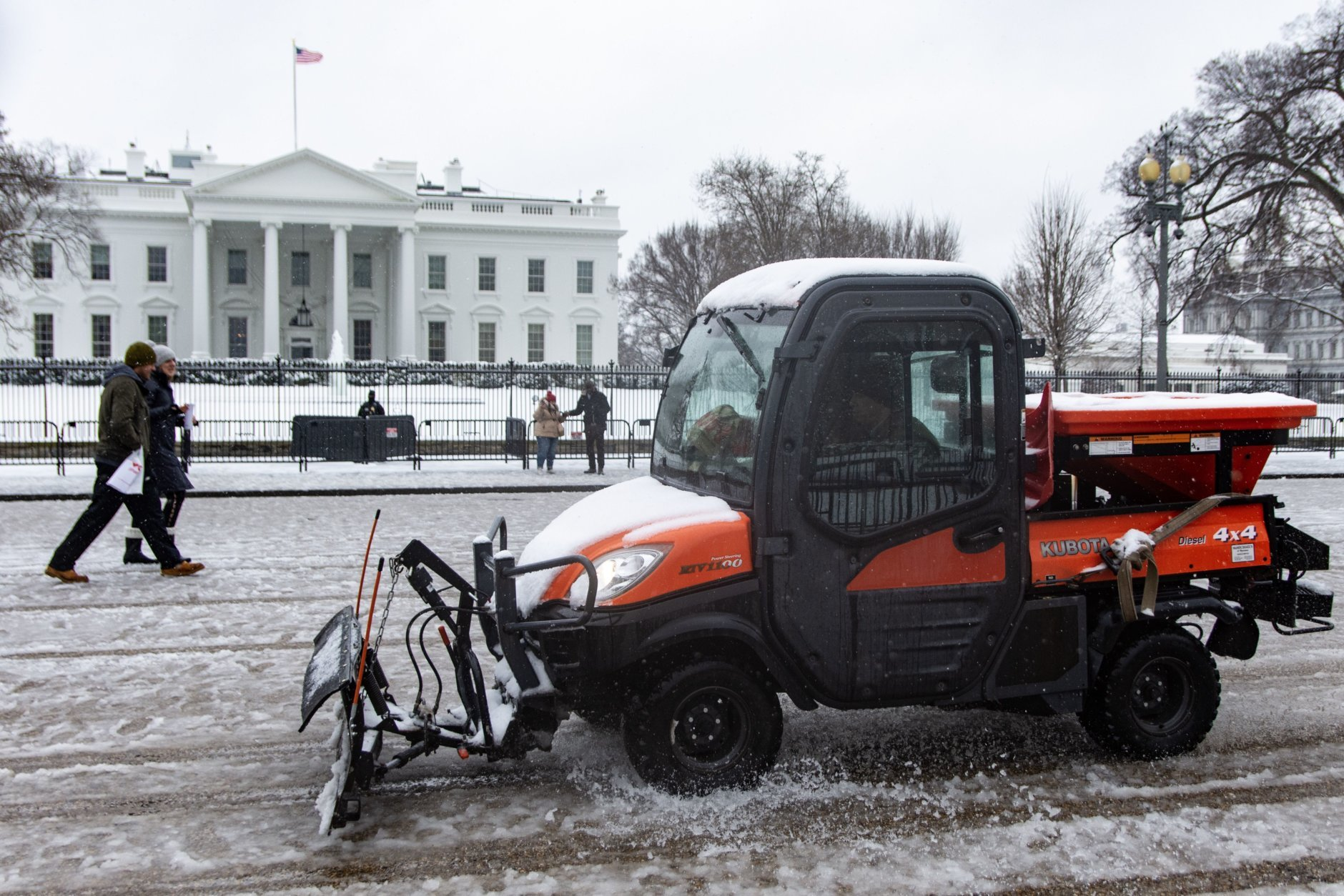 A small plow clears Pennsylvania Avenue outside the White House's north lawn on Wednesday. With the federal government closed, most of downtown D.C. was empty save for a few tourists snapping selfies in the snow. (WTOP/Alejandro Alvarez)