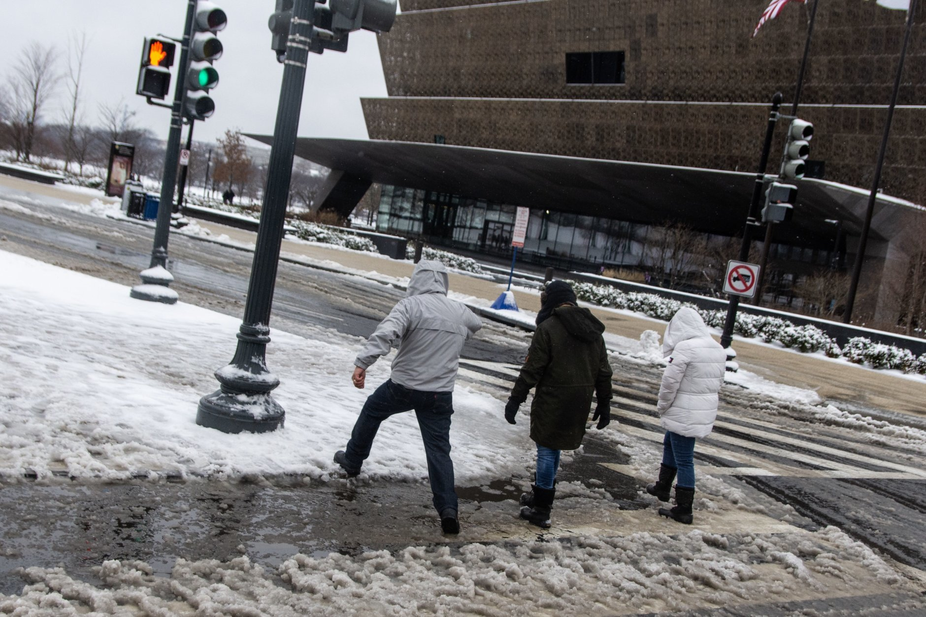 With a changeover to rain on Wednesday afternoon, half-melted slush pooled on most street corners along the National Mall, making life difficult for anybody hoping to keep their shoes dry. (WTOP/Alejandro Alvarez)