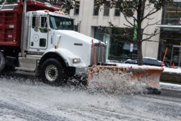 A snow plow clears slush off Connecticut Avenue on Wednesday afternoon. (WTOP/Alejandro Alvarez)