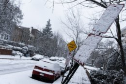 In northwest D.C.'s Kalorama Heights neighborhood, snow was sticking to roadside signs and vehicles by mid-morning Wednesday. (WTOP/Alejandro Alvarez)