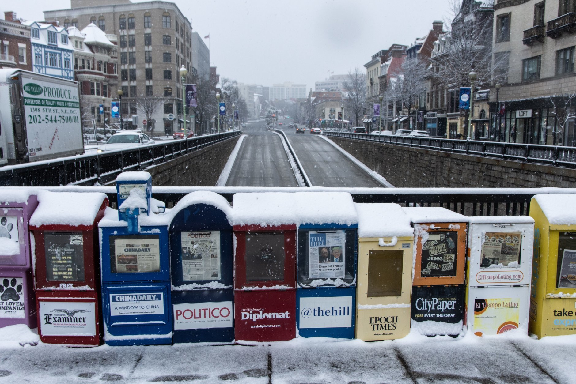 Newspaper stands in Dupont Circle, covered with snow. Visible is Connecticut Avenue looking northward. Most stores in the area were open as usual. (WTOP/Alejandro Alvarez)
