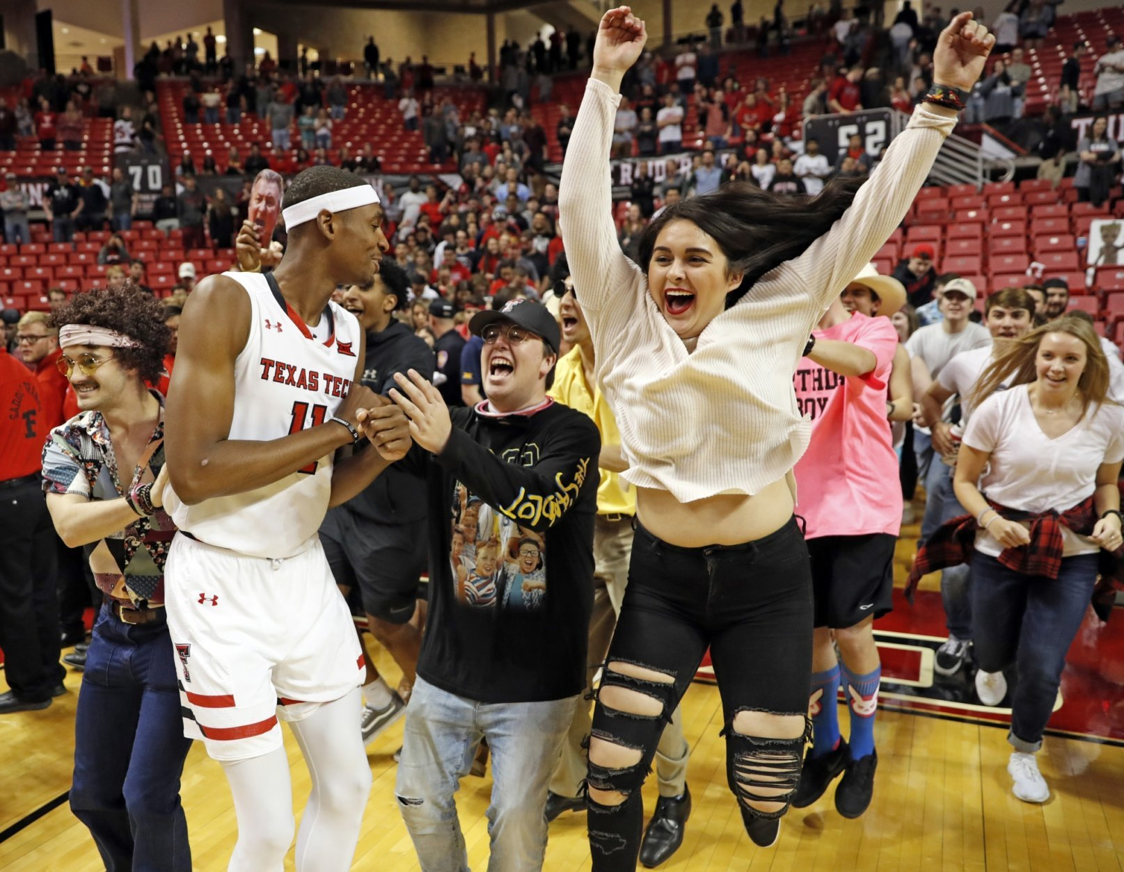 Texas Tech fans run onto the court to celebrate with Tariq Owens (11) and the rest of the team after an NCAA college basketball game against West Virginia, Monday, Feb. 4, 2019, in Lubbock, Texas. Texas Tech won 81-50. (AP Photo/Brad Tollefson)