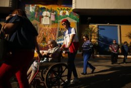 An election volunteer helps a woman in a wheelchair reach her voting table during the presidential election in San Salvador, El Salvador, Sunday, Feb. 3, 2019. Voters are choosing from among a handful of presidential candidates all promising to end corruption, stamp out gang violence and create more jobs in the Central American nation. (AP Photo/Salvador Melendez)