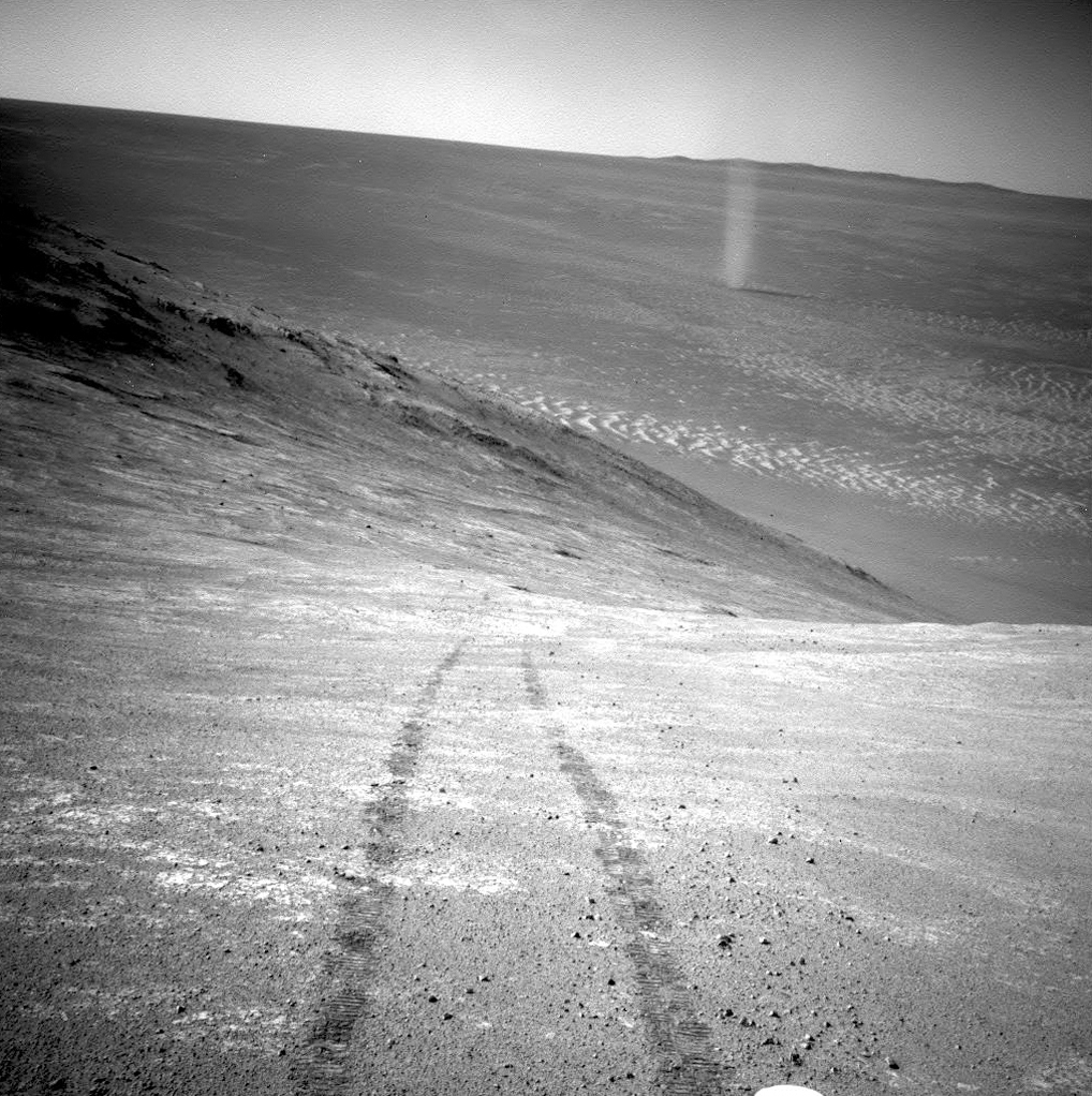 """This March 31, 2016 photo made available by NASA shows a dust devil in a valley on Mars, seen by the Opportunity rover perched on a ridge. The view looks back at the rover's tracks leading up the north-facing slope of """"Knudsen Ridge,"""" which forms part of the southern edge of """"Marathon Valley."""" (NASA/JPL-Caltech via AP)"""