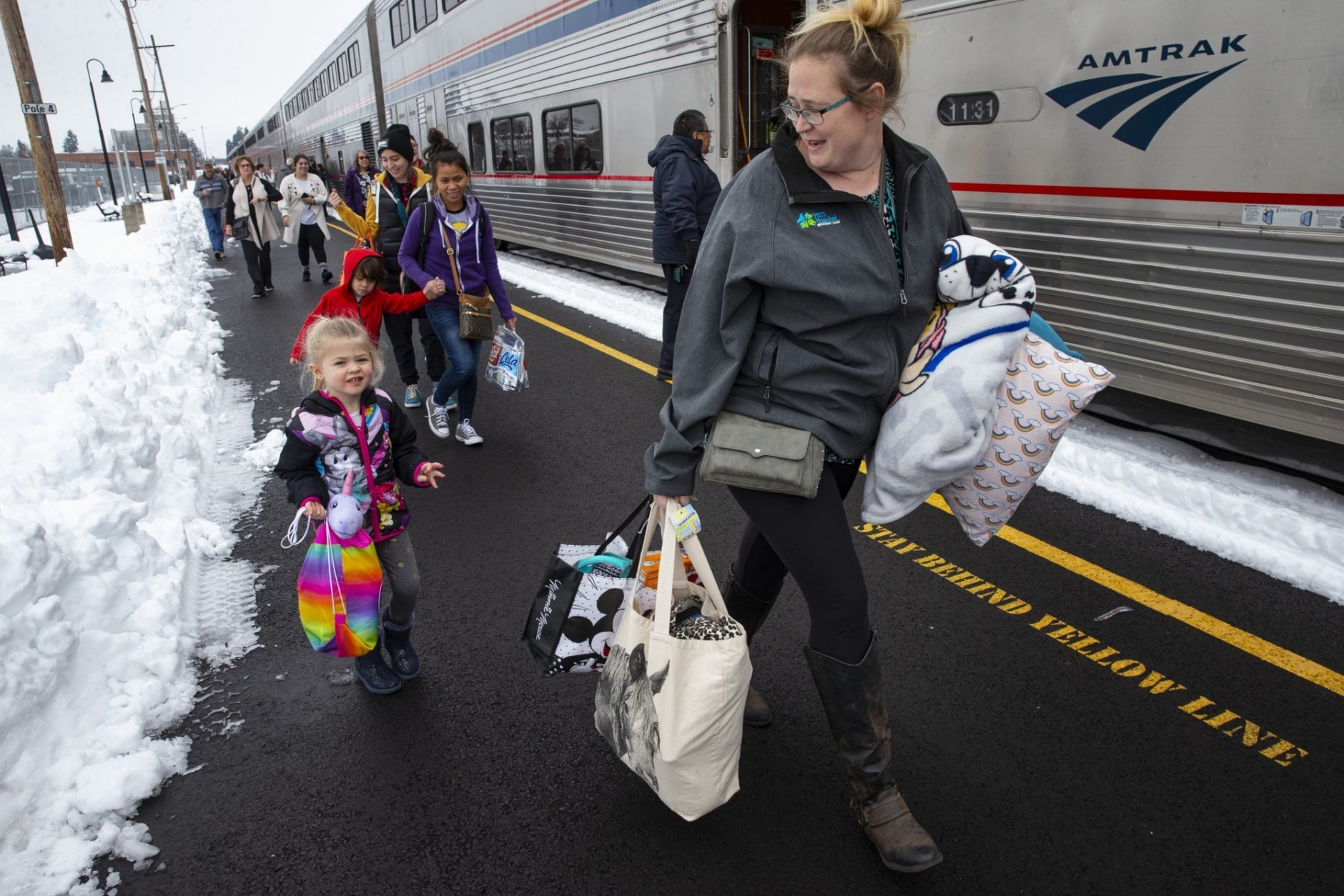Jordyn Hooper, right, and her four-year-old daughter Quinn Hooper, left, join other passengers as they disembark from an Amtrak train in Eugene, Ore, Tuesday, Feb. 26, 2019 after being stranded overnight in the mountains east of town. (AP Photo/Chris Pietsch)